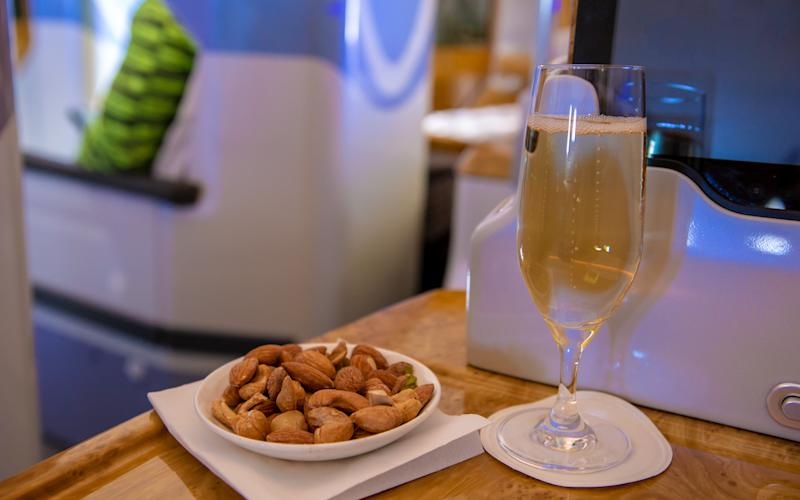 An assortment of warm nuts and champagne are offered to premium passengers.  | Talia Avakian