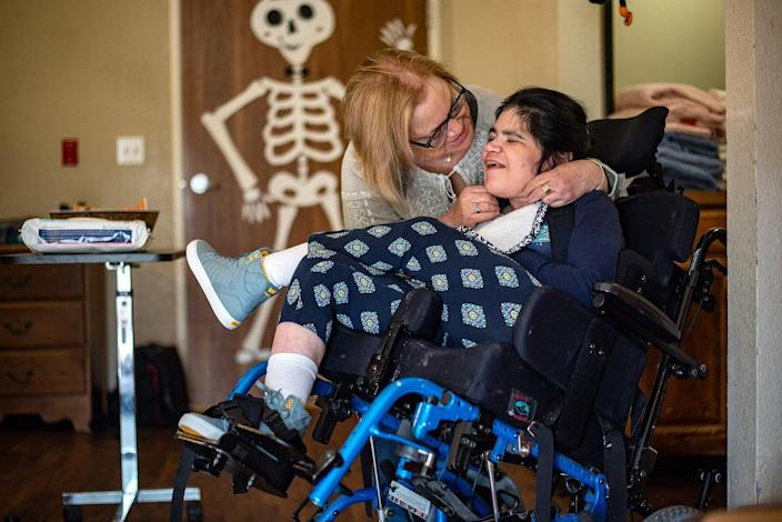 Sue Schnars embraces her daughter, Ivana, in her room at the Pflugerville Health Care Center in 2018.