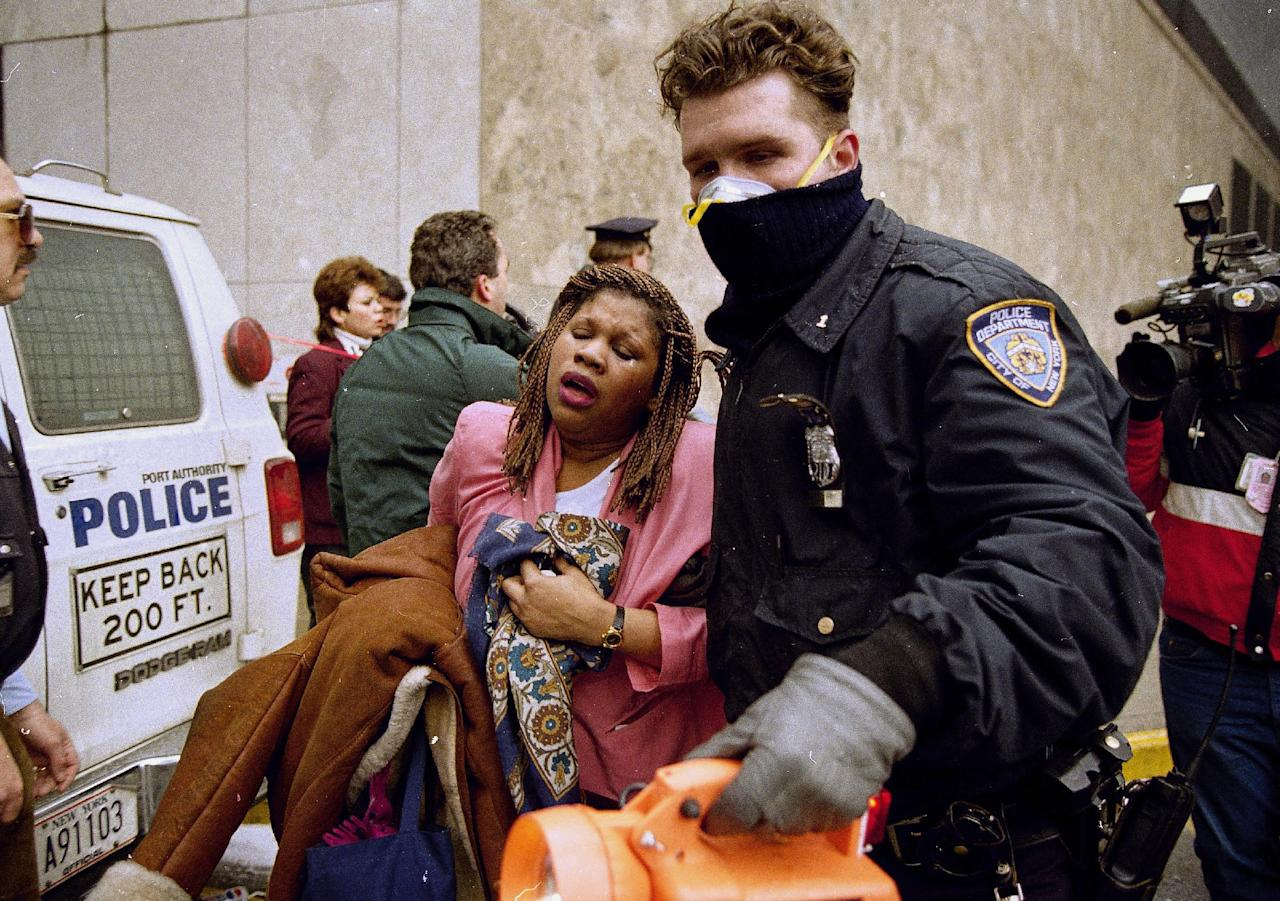 FILE - In this file photo of Feb. 26, 1993, a New York City police officer leads a woman to safety following a bomb blast at the World Trade Center. Twenty years ago a group of terrorists blew up explosives in an underground parking garage under one of the towers, killing six people and ushering in an era of terrorism on American soil. (AP Photo/Alex Brandon, File)