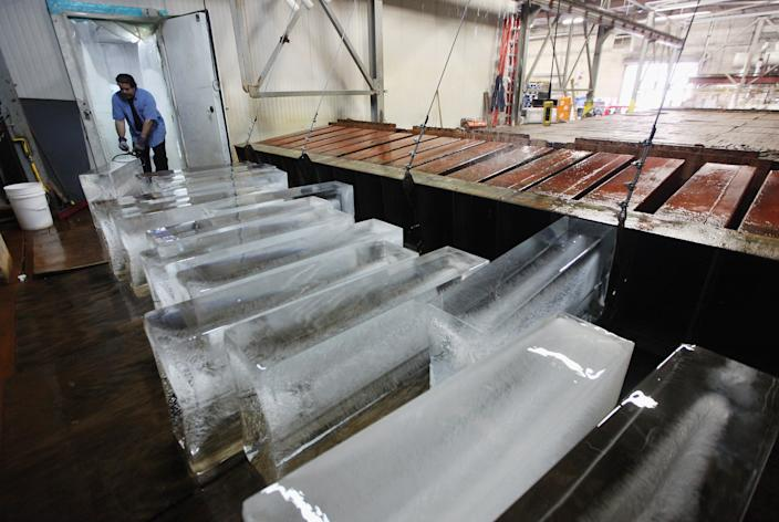 """Ricky Perez unloads 300-pound blocks of ice from a brine tank to be sold at Arctic Glacier Premium Ice on July 17, 2012 in the Bronx borough of New York City. Perez said, """"Right now we are selling these things like crazy."""" The blocks take three days to freeze in the tank and sell for $75. A heat advisory was issued in the city again today as high temperatures were expected in the 90?s though tomorrow. (Photo by Mario Tama/Getty Images)"""