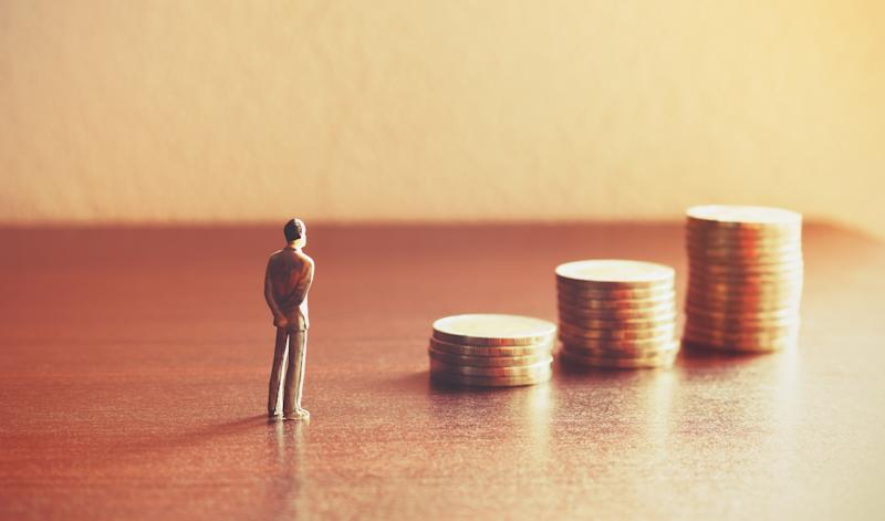 A small figurine of a man staring at an ascending stack of coins.