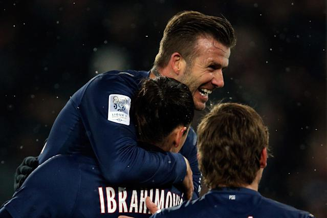 PARIS, FRANCE - FEBRUARY 24: David Beckham of PSG jumps on the goal scorer and team mate Zlatan Ibrahimovic during the Ligue 1 match between Paris Saint-Germain FC and Olympique de Marseille at Parc des Princes on February 24, 2013 in Paris, France. (Photo by Dean Mouhtaropoulos/Getty Images)