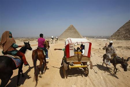 Egyptian tourists ride on horses at the Giza Pyramids, on the outskirts of Cairo