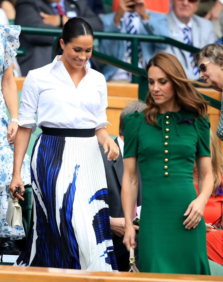 """<p>While watching Serena Williams compete at Wimbledon alongside Kate Middleton, Meghan wore a white Givenchy button down with a colorful pleated <a href=""""https://www.hugoboss.com/us/a-line-skirt-in-portuguese-plisse-fabric-with-overprinted-motif/hbna50411310_965.html"""" target=""""_blank"""">Hugo Boss skirt</a>. </p>"""
