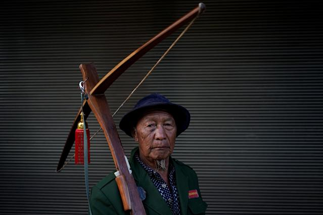 "An ethnic Lisu man carries his crossbow as he poses for a photograph during a crossbow shooting competition in Luzhang township of Nujiang Lisu Autonomous Prefecture in Yunnan province, China, March 29, 2018. REUTERS/Aly Song SEARCH ""SONG CROSSBOW"" FOR THIS STORY. SEARCH ""WIDER IMAGE"" FOR ALL STORIES. TPX IMAGES OF THE DAY."