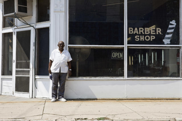 <p>A well-dressed barber stands in front of his barbershop. </p>