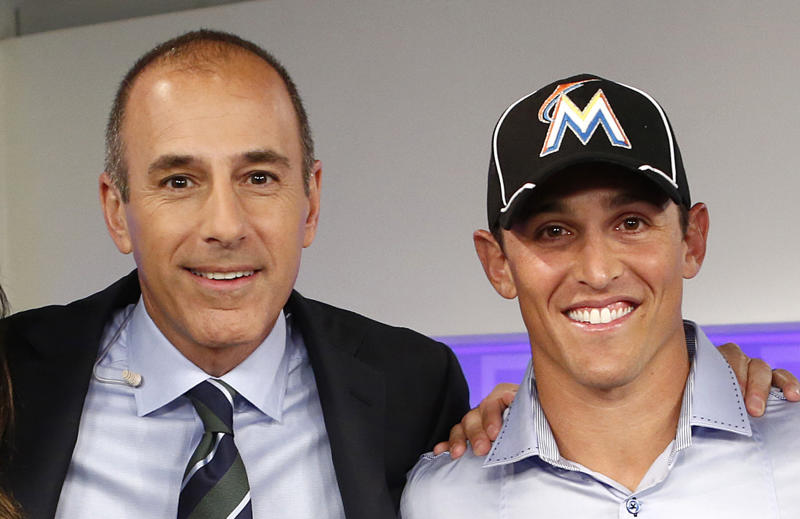 """This image released by NBC shows host Matt Lauer, left, posing with Adam Greenberg after an appearance on the """"Today"""" show, Thursday, Sept. 27, 2012 in New York. The Marlins said Thursday that they have signed Greenberg to a one-day contract, effective Oct. 2, and will play him that day against the New York Mets. Greenberg made his big-league debut for the Chicago Cubs on July 9, 2005 against the Marlins, getting one plate appearance but no official at-bat after a 92 mph fastball that struck him in the head. Greenberg was the subject of a campaign called """"One At Bat,"""" which lobbied teams to give him a second chance. The Marlins publicly extended the invitation to Greenberg on NBC's """"Today"""" show Thursday morning. (AP Photo/NBC NewsWire, Peter Kramer)"""