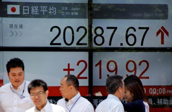 FILE PHOTO: People walk past an electronic board showing Japan's Nikkei average outside a brokerage in Tokyo, Japan June 20, 2017. REUTERS/Toru Hanai/File Photo