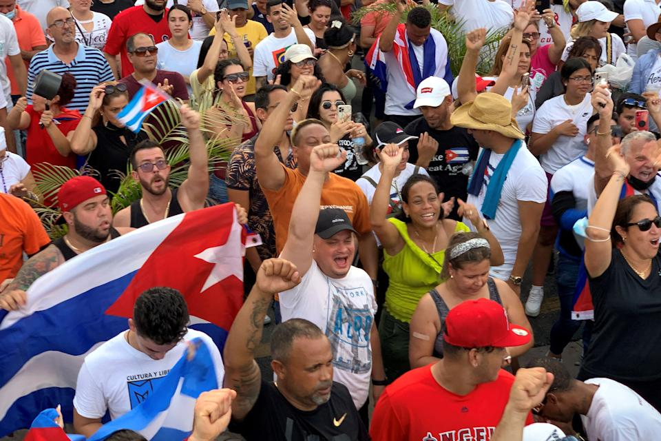 People demonstrate, some holding Cuban and US National flags, during a protest against the Cuban government in Miami on July 11, 2021. - Thousands of Cubans across the country took part in rare protests July 11, 2021, against the communist government, marching through several towns chanting,