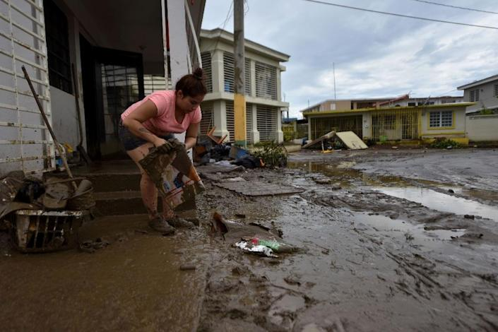 A woman removes mud from her damaged house in Toa Baja, near San Juan, Puerto Rico (AFP Photo/HECTOR RETAMAL)