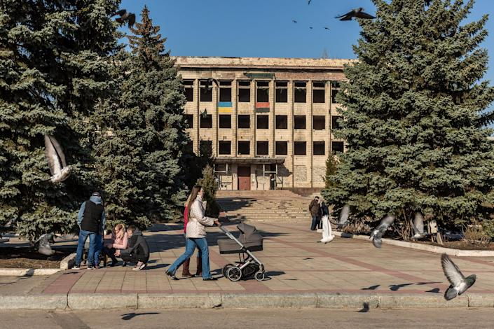 Image: Local residents walk near the former city council building, which was destroyed years ago during the fighting in Toretsk. (Oksana Parafeniuk / for NBC News)