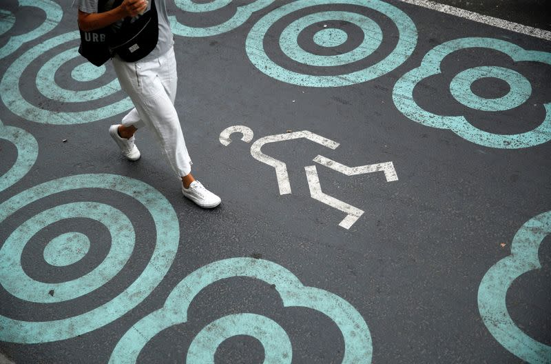 A woman walks by a pedestrian zone painted in blue at Pelai street in Barcelona