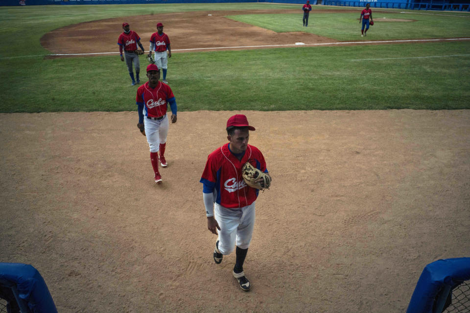 Several Cuban baseball players walk on the field during a break from the training session at the Estadio Latinoamericano in Havana, Cuba, Tuesday, May 18, 2021. A little over a week after the start of the Las Americas Baseball Pre-Olympic in Florida, the Cuban team does not have visas to travel to the United States. (AP Photo/Ramon Espinosa)