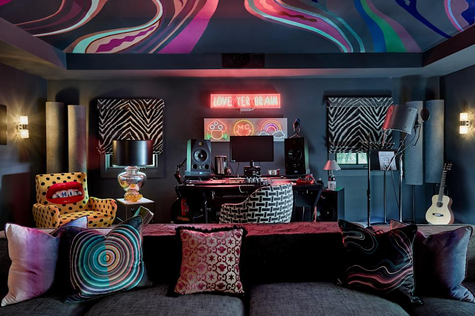 "Miley's studio is ""definitely a vibe."" The trippy ceiling was painted by surface designer Brian Robles, and it has multiple inspirations. Says Tish, ""It started with the throw pillows. I had found those at Barneys before Barneys went out of business. I just knew at some point, Miley's going to need these."" When Tish and Sanders suggested they play off the colorful waves in the pillows' psychedelic designs for the mural, Tish says, ""Miley agreed, then added, 'Yeah, but it should also feel like vaginas.' I was like, Okay!"" The zebra-print fabric on the window shades is from Jim Thompson Fabrics. A series of vintage 1960s Targetti Sankey sconces punctuate the space."