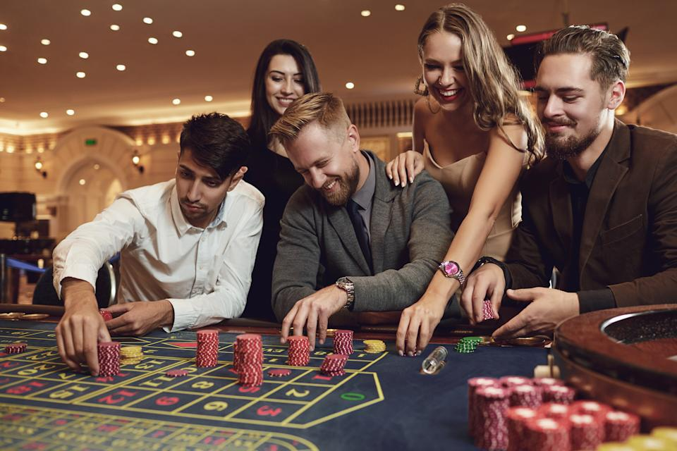 Happy friends play roulette in a casino. Gambling Betting.