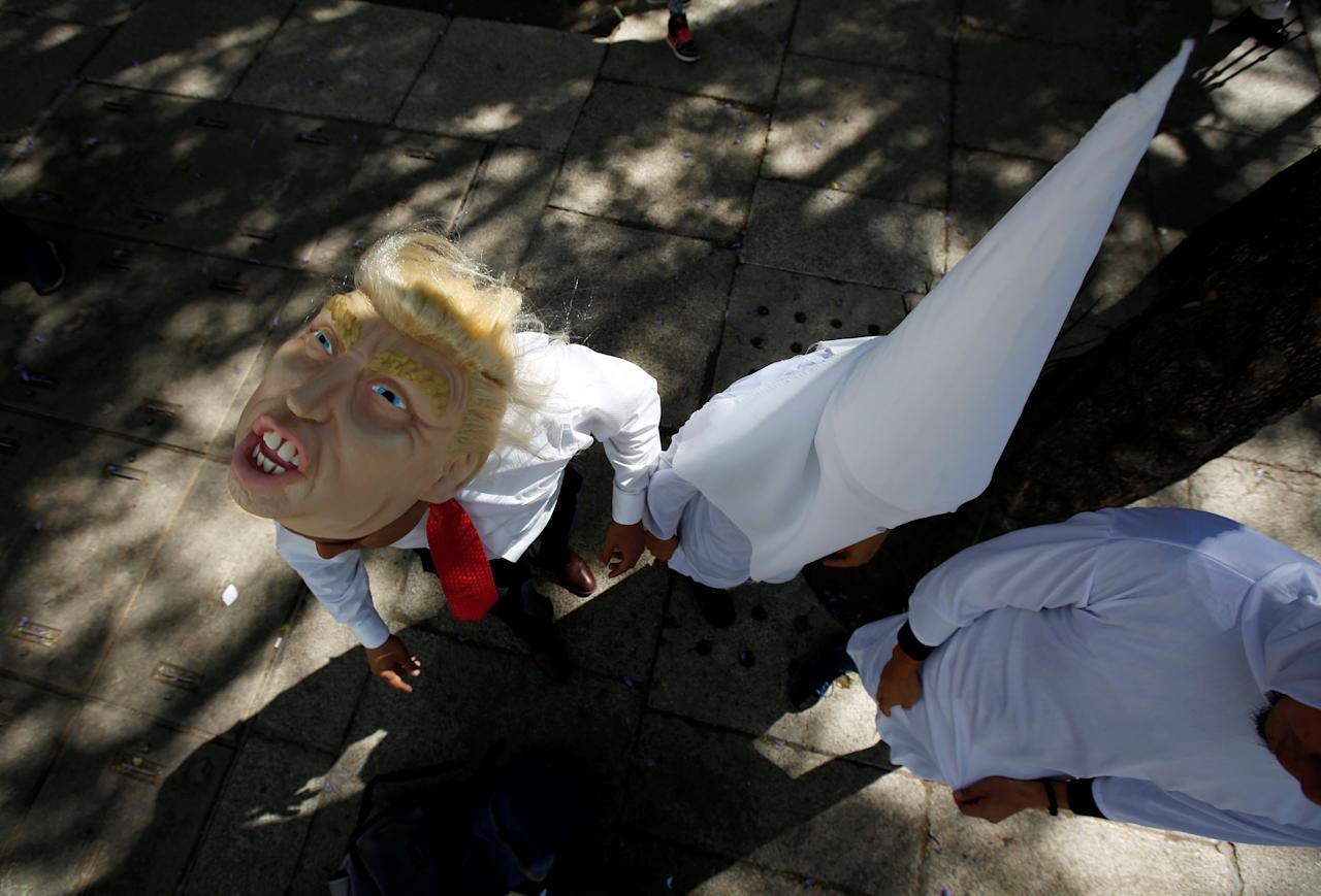 Actors impersonating U.S. President Donald Trump and members of the Ku Klux Klan get ready for a performance on behalf of a local Mexican political party during a protest against Trump, in Mexico City, Mexico February 20, 2017.   REUTERS/Jose Luis Gonzalez