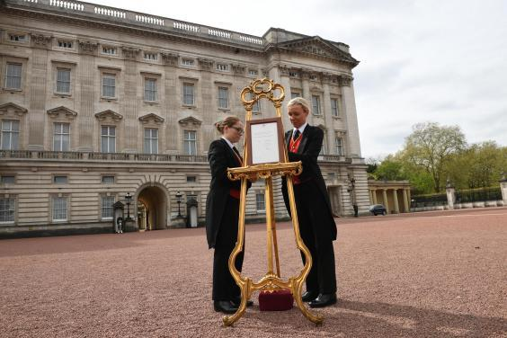 Senior footman Olivia Smith (L) and footman Heather McDonald place a notice on an easel in the forecourt of Buckingham Palace in London to formally announce the birth of a baby boy to the Duke and Duchess of Cambridge at the Lindo Wing of St Mary's Hospital on April 23, 2018 in London, England (Getty Images)