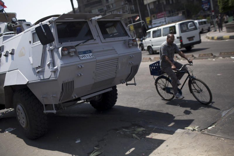 An Egyptian man rides a bicicle past an armored vehicle protecting a bridge between Tahrir Square and Cairo University, where Muslim Brotherhood supporters have gathered, in Giza, Egypt, Wednesday, July 3, 2013. Egypt's leading democracy advocate Mohamed ElBaradei and top Muslim and Coptic Christian clerics met Wednesday with the army chief to discuss a political road map for Egypt only hours before a military ultimatum to the Islamist president was set to expire. (AP Photo/ Manu Brabo)