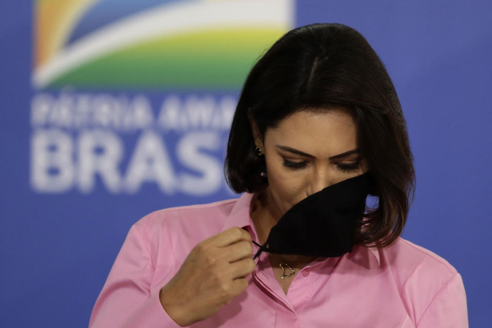 Brazil's first lady Michelle Bolsonaro removes her mask amid the COVID-19 pandemic in order to speak at an event promoting a government campaign against domestic violence at Planalto presidential palace in Brasilia, Brazil, Friday, May 15, 2020. (AP Photo/Eraldo Peres)