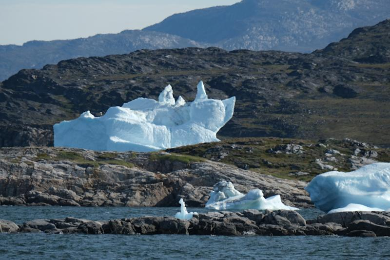An iceberg that looks like a reclining cat stands in a cove during unseasonably warm weather near Ilulissat, Greenland. (Photo: Sean Gallup/Getty Images)