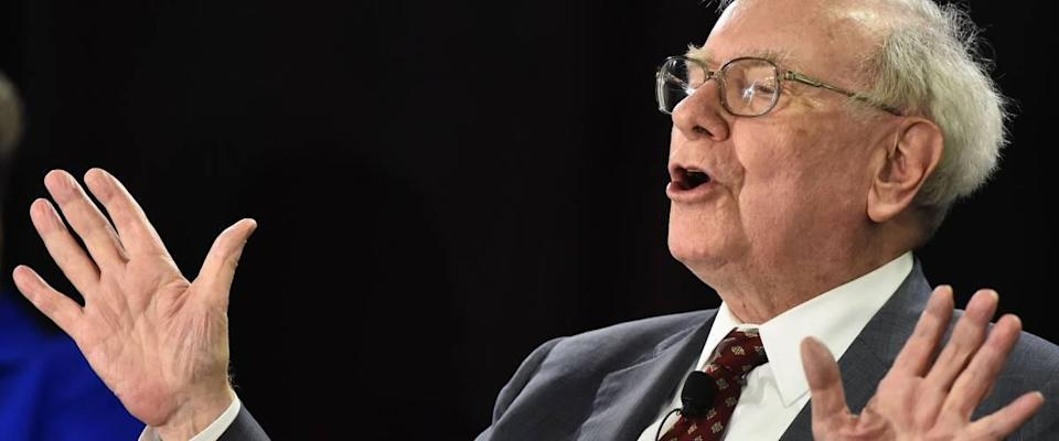 Warren Buffett speaks with hands up, gesturing