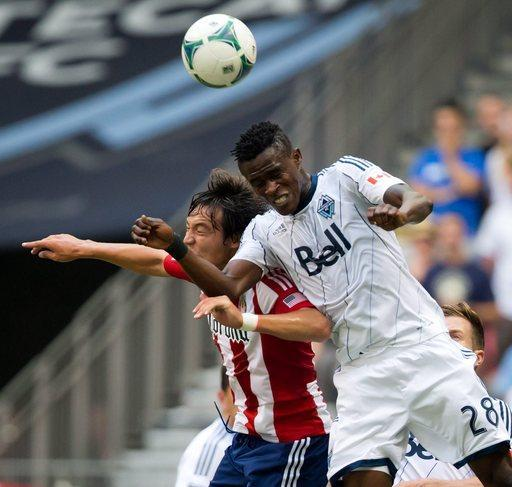 Vancouver Whitecaps' Gershon Koffie, right, of Ghana, and Chivas USA's Erick Torres, of Mexico, battle for the ball during the first half of an MLS soccer game, Sunday, Sept. 1, 2013 in Vancouver, British Columbia. (AP Photo/The Canadian Press, Darryl Dick)