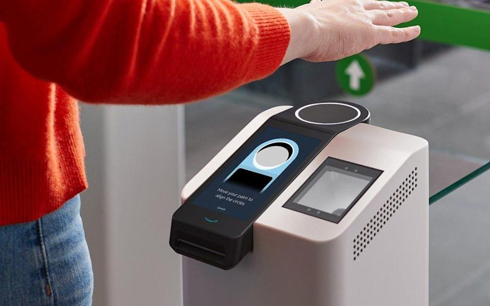 A seemingly computer-generated image of the new scanner installed into a grey podium at the doors of a supermarket, with a person in a bright orange wooly jumper reaching out to hold their hand out flat over the pad - Amazon