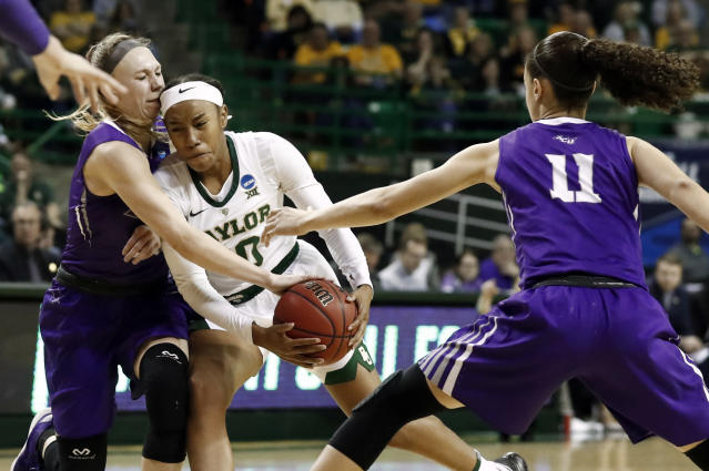 Abilene Christian guard Breanna Wright, left, and Sara Williamson (11) defend as Baylor guard Juicy Landrum (20) drives to the basket in the second half of a first-round game in the NCAA women's college basketball tournament in Waco, Texas, Saturday March 23, 2019. (AP Photo/Tony Gutierrez)