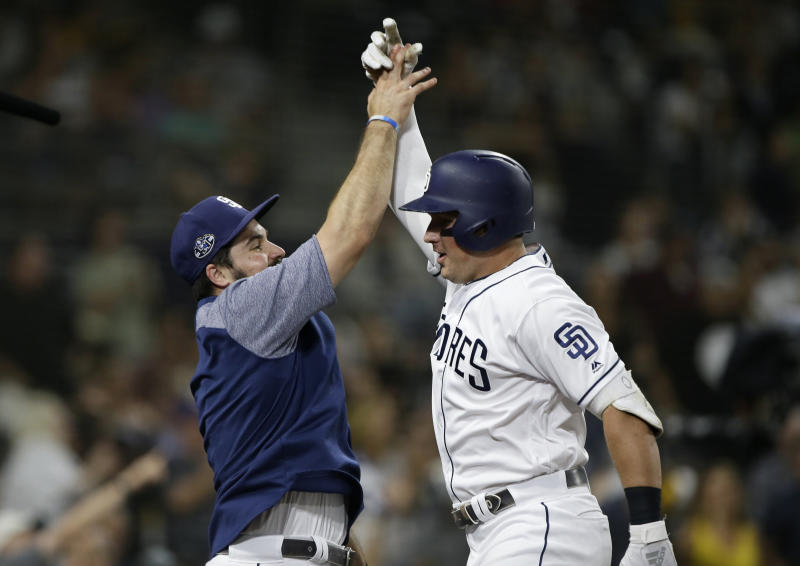 San Diego Padres' Austin Hedges, left, congratulates Hunter Renfroe, right, after Renfroe hit a solo home run, during the fifth inning of a baseball game against the Arizona Diamondbacks in San Diego, Saturday, Sept. 21, 2019. (AP Photo/Alex Gallardo)