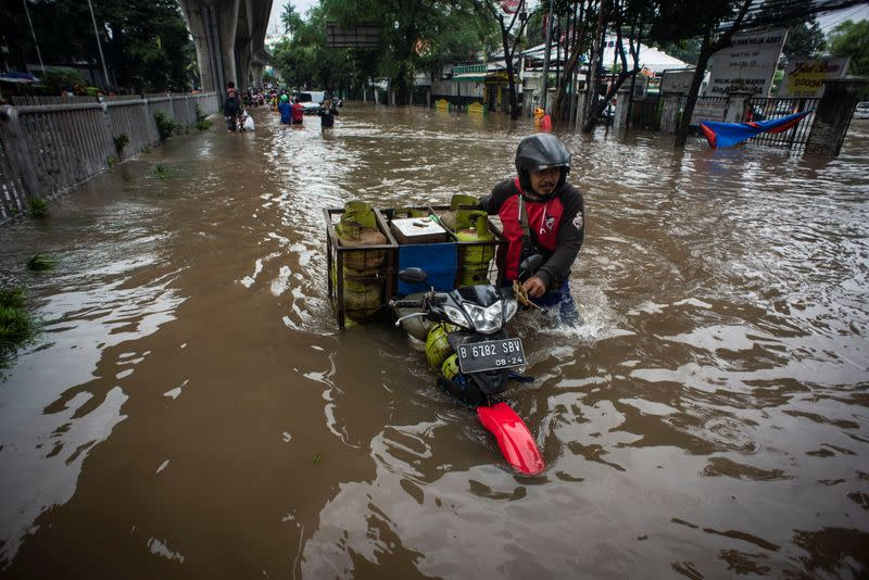 Man pushes his motorbike through water in an area affected by floods following heavy rains in Jakarta