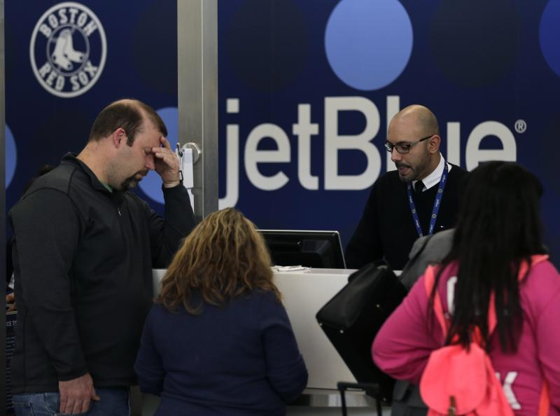 A traveler holds his forehead while waiting to rebook a cancelled JetBlue flight, Monday, Jan. 6, 2014, in Boston. JetBlue announced that they would halt operations in Boston, New York and New Jersey later in the afternoon, to rest their crews and give it time to service aircraft, due to flight delays and cancellations. Heavy rains in the East, and sub-zero temperatures in the Midwest, threw airlines and travel plans into havoc. (AP Photo/Charles Krupa)