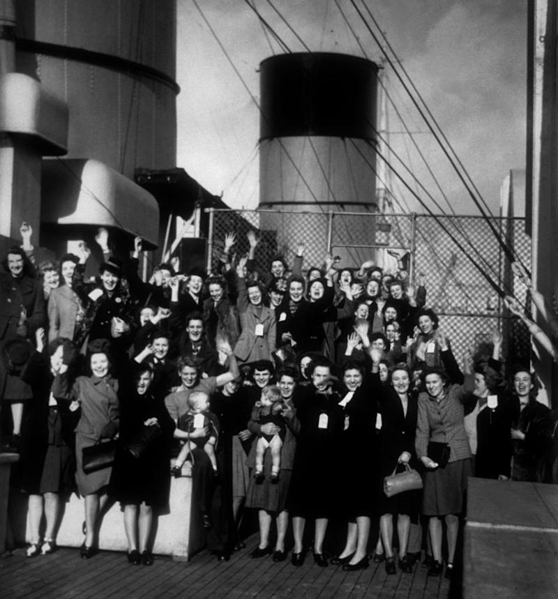 Alan Mogridge, being held by his mother who is waving, front row, fourth from left, on the Queen Mary.