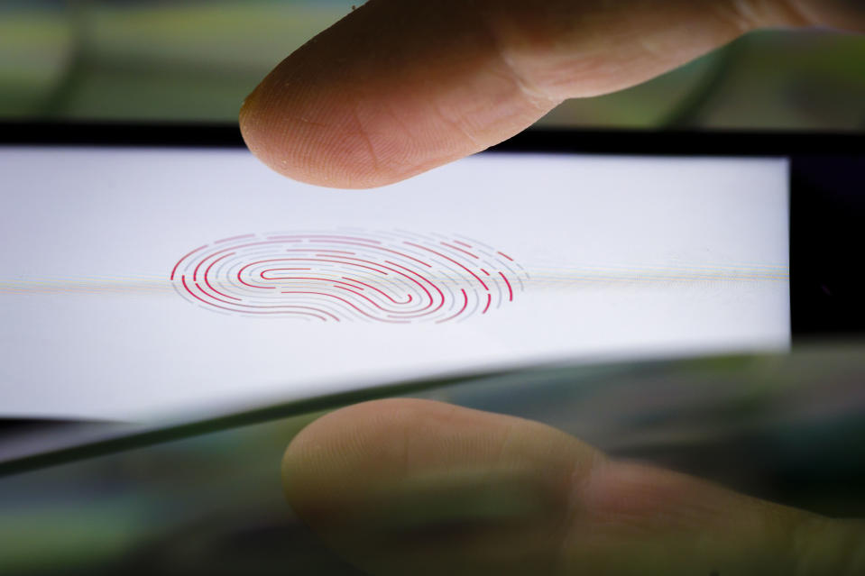 BERLIN, GERMANY - FEBRUARY 18: Symbol photo on the subject of Touch ID. A finger is held on the display of an Apple iPhone, on which the symbol of a fingerprint can be seen on February 18, 2020 in Berlin, Germany. (Photo by Thomas Trutschel/Photothek via Getty Images)