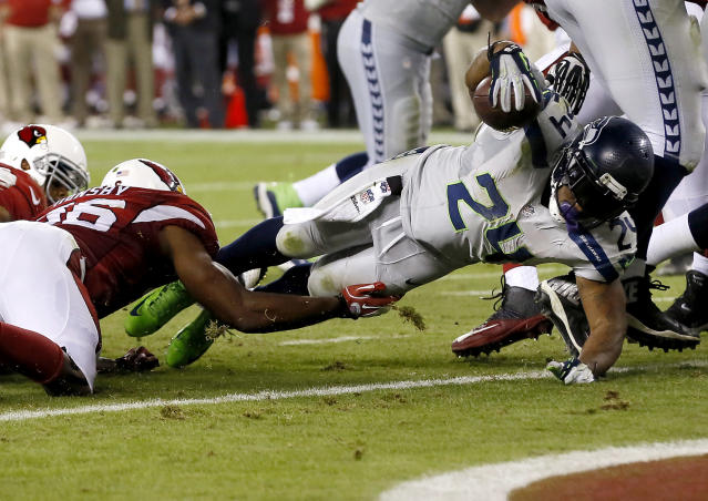 Seattle Seahawks running back Marshawn Lynch (24) falls into the end zone for a touchdown as Arizona Cardinals inside linebacker Karlos Dansby (56) defends during the second half of an NFL football game, Thursday, Oct. 17, 2013, in Glendale, Ariz. (AP Photo/Ross D. Franklin)