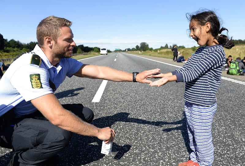 A Danish policeman plays with a girl as a group of migrants attempt to walk on the E45 freeway from Padborg, on the Danish-German border, towards Sweden on September 9, 2015 (AFP Photo/Claus Fisker)