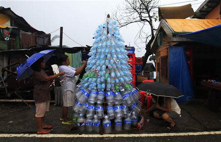 Victims of super Typhoon Haiyan decorate their improvised Christmas tree with empty cans and bottles at the ravaged town of Anibong, Tacloban city, central Philippines December 24, 2013, a month after Typhoon Haiyan battered central Philippines. REUTERS/Romeo Ranoco