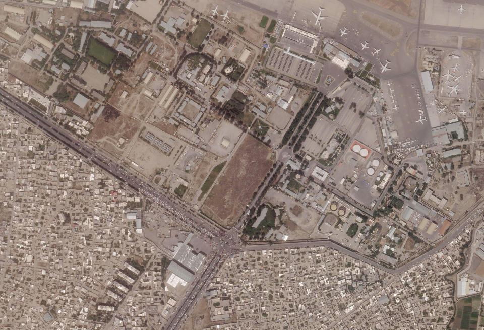 This satellite photo provided by Planet Labs Inc. shows vehicles trying to reach the civilian side of Kabul International Airport, also known as Hamid Karzai International Airport, Wednesday, Aug. 18, 2021. The Pentagon said Tuesday that U.S. commanders are communicating with the Taliban as they work to evacuate thousands of people through the airport. The Taliban cleared the civilian side of the airport Tuesday and control access to it. (Planet Labs Inc. via AP)