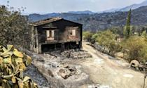 A charred house stands in the village of Ora in the Larnaca district of Cyprus on Sunday morning
