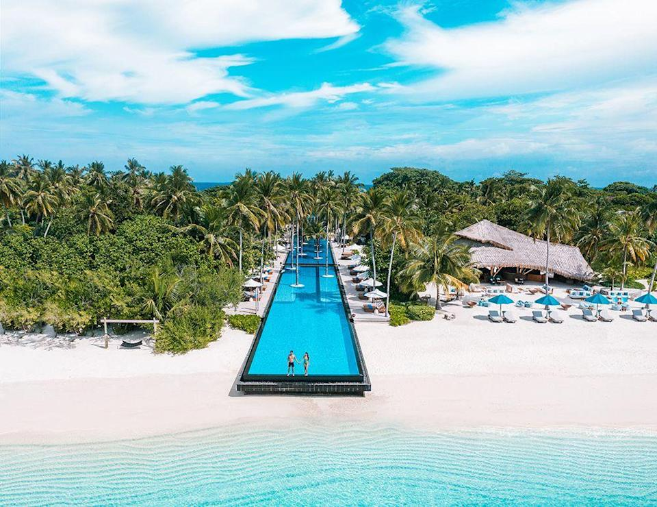 """<p>The infinity pool at <a href=""""https://www.fairmont-maldives.com"""" rel=""""nofollow noopener"""" target=""""_blank"""" data-ylk=""""slk:Fairmont Maldives"""" class=""""link rapid-noclick-resp"""">Fairmont Maldives</a> is the longest swimming pool in the archipelago and stretches the entire width of the private island. Like, wow. Oh to be one half of that couple perching on the edge.</p>"""