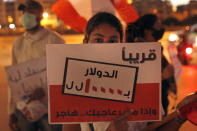 """A protester holds an Arabic placard that reads: """"Soon $ 1 = 10,000 Lebanese pounds and if you are not happy, immigrate,"""" during a protest against the economic and financial crisis, in front of the government house in downtown Beirut, Lebanon, Thursday, June 11, 2020. The Lebanese pound has hit a record low against the dollar on the black market as the country's political crisis deepens and foreign currency reserves dwindle further. (AP Photo / Hussein Malla)"""