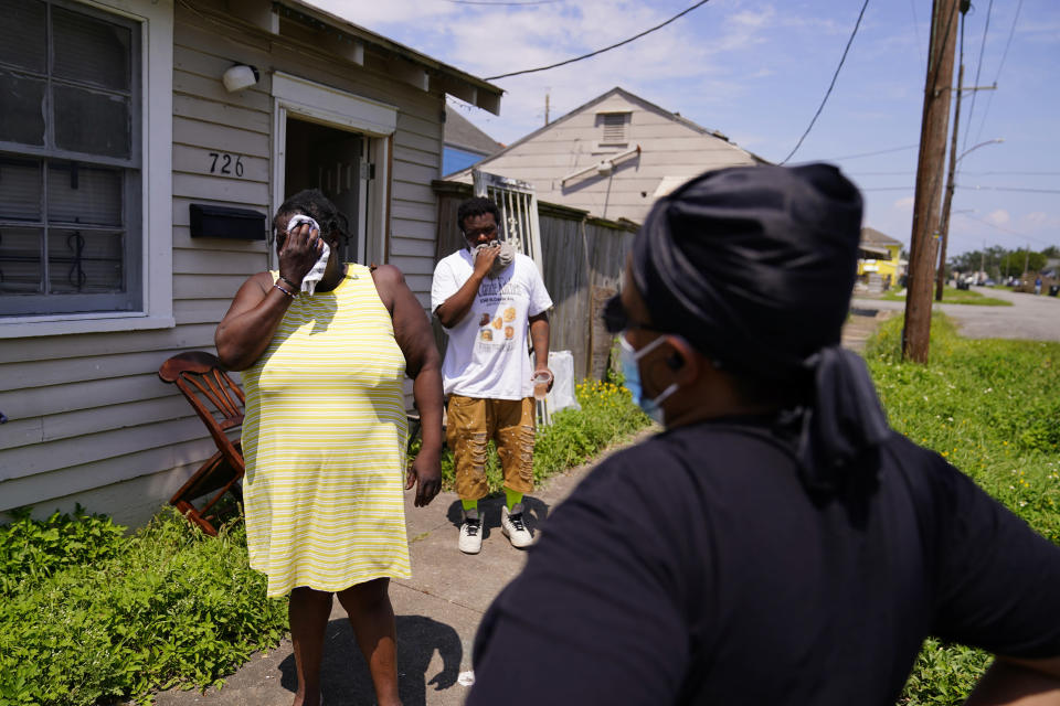 In this Sept. 4, 2021, photo, Lationa Kemp, 57, left, and her son, Alvin Kemp, 25, center, pause as they talk with housing advocate Andreanecia Morris outside their rental home in the aftermath of Hurricane Ida in the Lower Ninth Ward of New Orleans. (AP Photo/Matt Slocum)