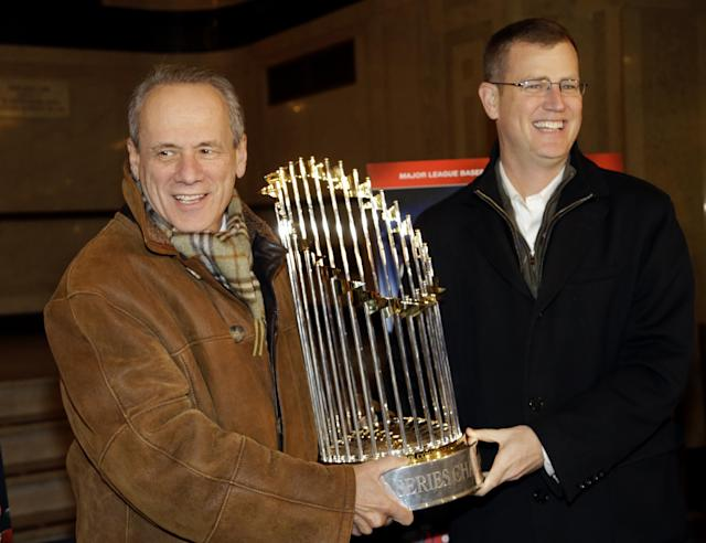 "FILE - In this Nov. 23, 2013 file photo, Boston Red Sox CEO Larry Lucchino, left, and Chief Operating Officer Sam Kennedy hold the 2013 World Series baseball trophy on the red carpet at the Wang Theatre before a screening of a DVD about the series in Boston. Lucchino said Friday, Feb. 21, 2014, that he views the big-spending New York Yankees and his more frugal team as ""very different animals."" (AP Photo/Steven Senne, File)"