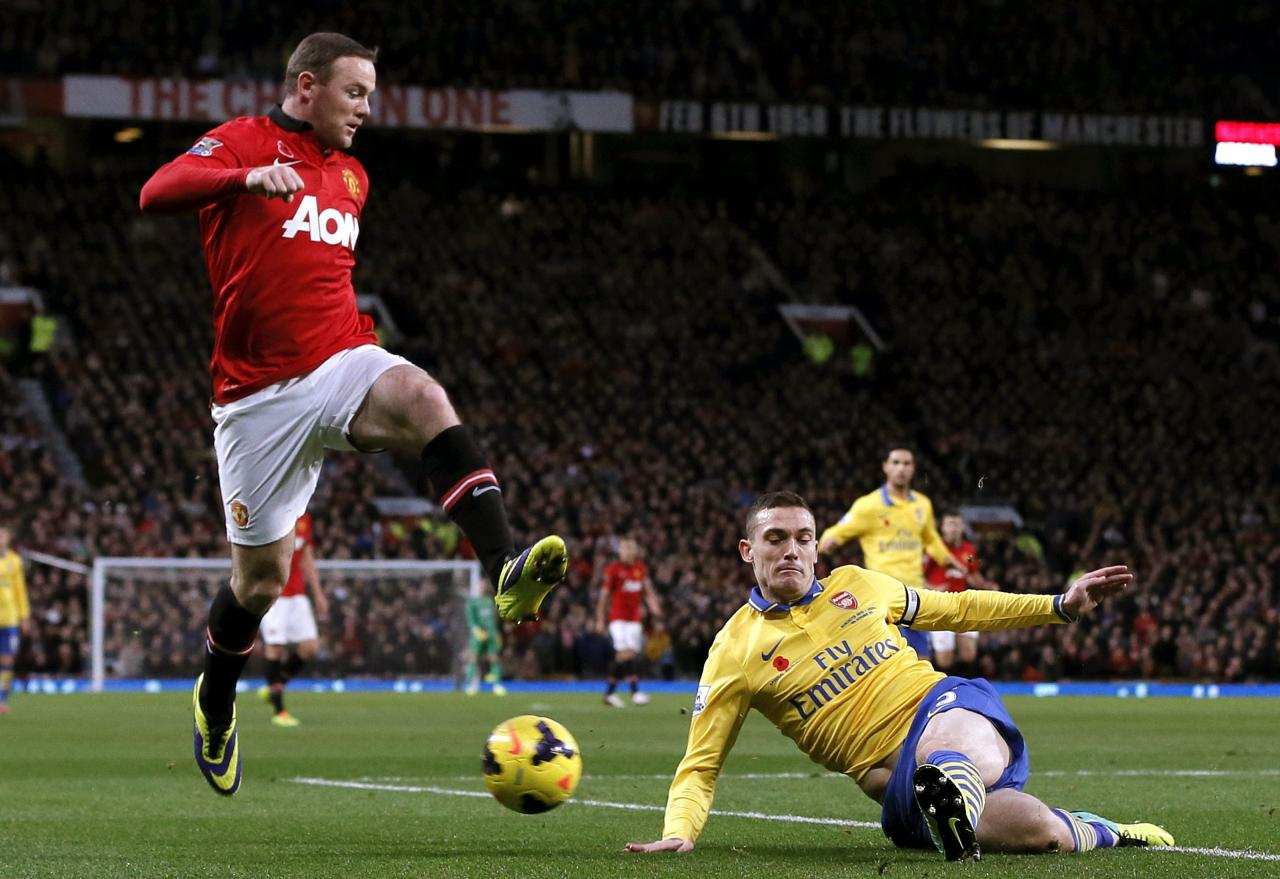 Arsenal's Vermaelen challenges Manchester United's Rooney during their English Premier League soccer match in Manchester