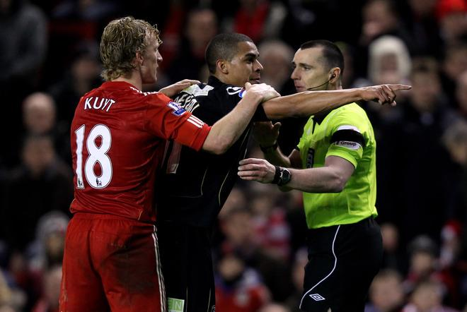 LIVERPOOL, ENGLAND - JANUARY 06:  Tom Adeyemi of Oldham Athletic is restrained by Dirk Kuyt of Liverpool after being abused by fans on the Kop during the FA Cup 3rd Round match between Liverpool and Oldham Athletic at Anfield on January 6, 2012 in Liverpool, England.  (Photo by Alex Livesey/Getty Images)