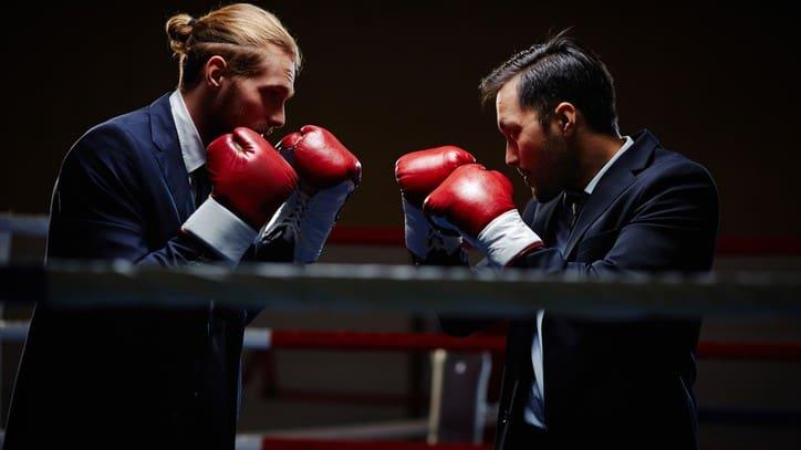 Two businessmen in a boxing ring ready to spar