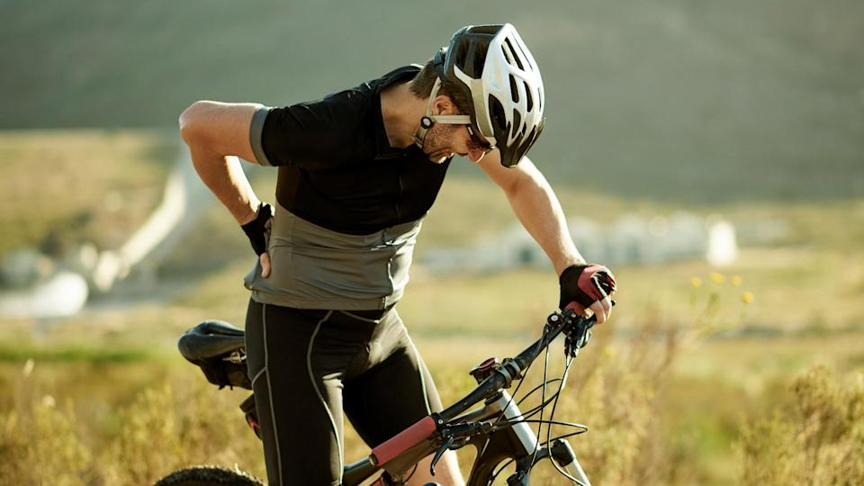 Shot of a mature man experiencing back pain while out for a ride on his mountain bike.