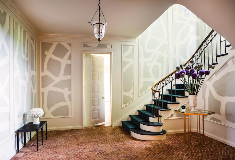 """<div class=""""caption""""> The foyer is the most dramatic transformation in the home. Previously, it had all been done in shades of brown. The designer brightened up the space by first painting the walls <a href=""""https://www.benjaminmoore.com/en-us"""" rel=""""nofollow noopener"""" target=""""_blank"""" data-ylk=""""slk:Benjamin Moore"""" class=""""link rapid-noclick-resp"""">Benjamin Moore</a>'s Feather Down—a cool white hue—and then placed a gray-and-white-patterned wallpaper made of Japanese tea paper by <a href=""""https://porterteleo.com/"""" rel=""""nofollow noopener"""" target=""""_blank"""" data-ylk=""""slk:Porter Teleo"""" class=""""link rapid-noclick-resp"""">Porter Teleo</a> in the molding panels. The entryway table is from <a href=""""https://www.interludehome.com/"""" rel=""""nofollow noopener"""" target=""""_blank"""" data-ylk=""""slk:Interlude Home"""" class=""""link rapid-noclick-resp"""">Interlude Home</a> and the low table is a one-of-a-kind piece from <a href=""""https://www.stephanehubert.com/"""" rel=""""nofollow noopener"""" target=""""_blank"""" data-ylk=""""slk:Stephane Hubert Design"""" class=""""link rapid-noclick-resp"""">Stephane Hubert Design</a>. </div>"""
