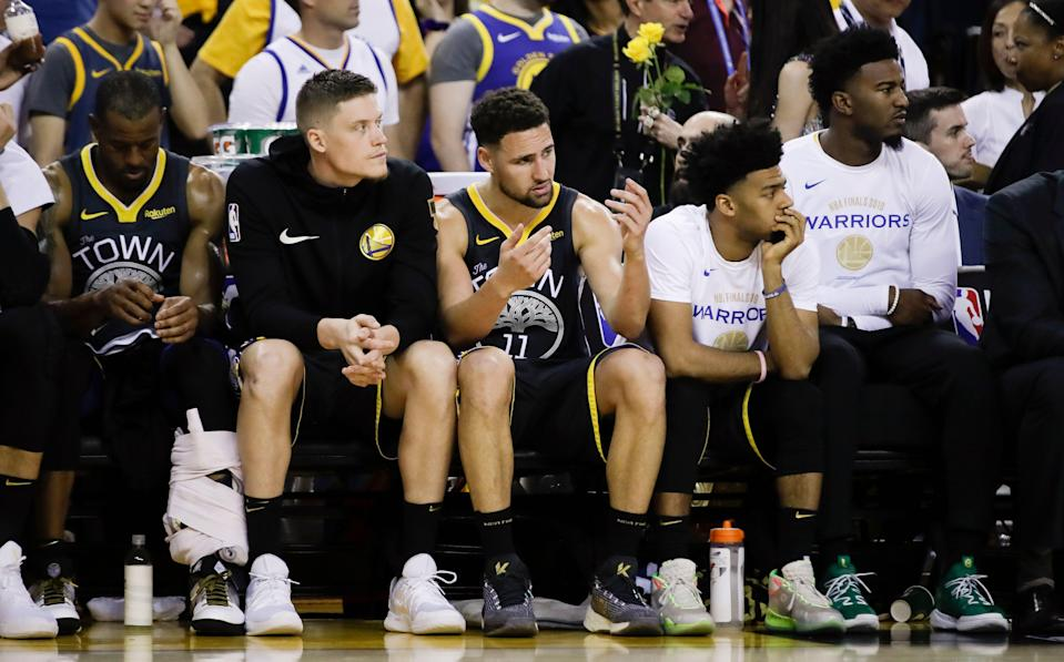 Golden State Warriors' Andre Iguodala, from left, sits on the bench with Jonas Jerebko, Klay Thompson, Quinn Cook and Jordan Bell during the second half of Game 4 of basketball's NBA Finals against the Toronto Raptors in Oakland, Calif., Friday, June 7, 2019. (AP Photo/Ben Margot)