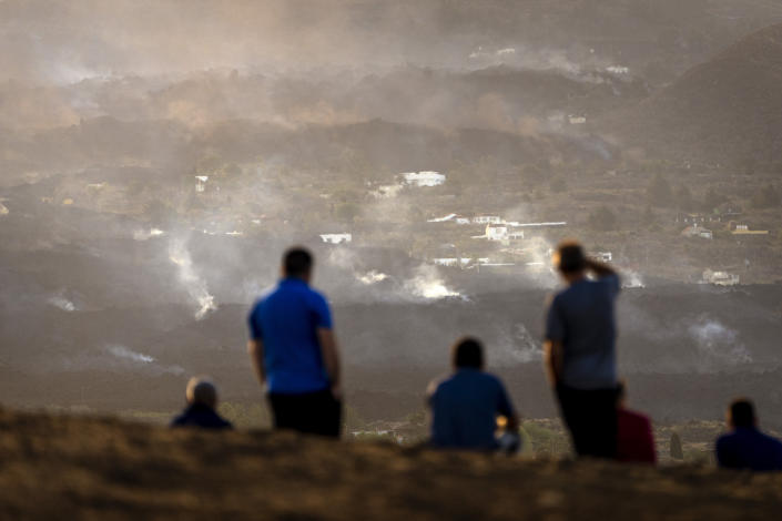 Residents look from a hill as the lava from a volcano eruption flows on the island of La Palma in the Canaries, Spain, Friday, Sept. 24, 2021. A volcano on a small Spanish island in the Atlantic Ocean erupted on Sunday, forcing the evacuation of thousands of people. Experts say the volcanic eruption and its aftermath on a Spanish island could last for up to 84 days. (AP Photo/Emilio Morenatti)