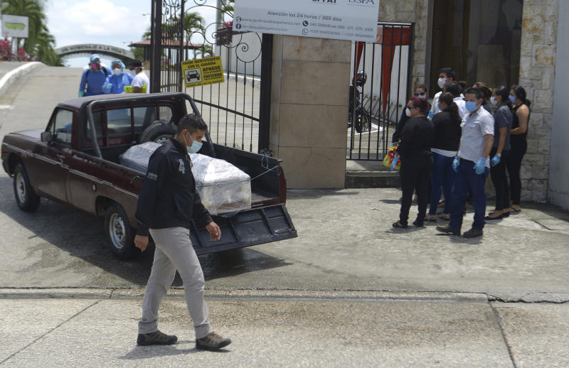 Relatives watch as the remains of a coronavirus victim, which authorities wrap in plastic, arrive to the Jardines de la Esperanza cemetery in Guayaquil, Ecuador, Wednesday, April 1, 2020. Ecuador has one of the highest numbers of confirmed coronavirus cases and deaths in the region, combined with a lack of ventilators, hospital beds and experienced crisis management. (AP Photo/Andrea Aguilar)